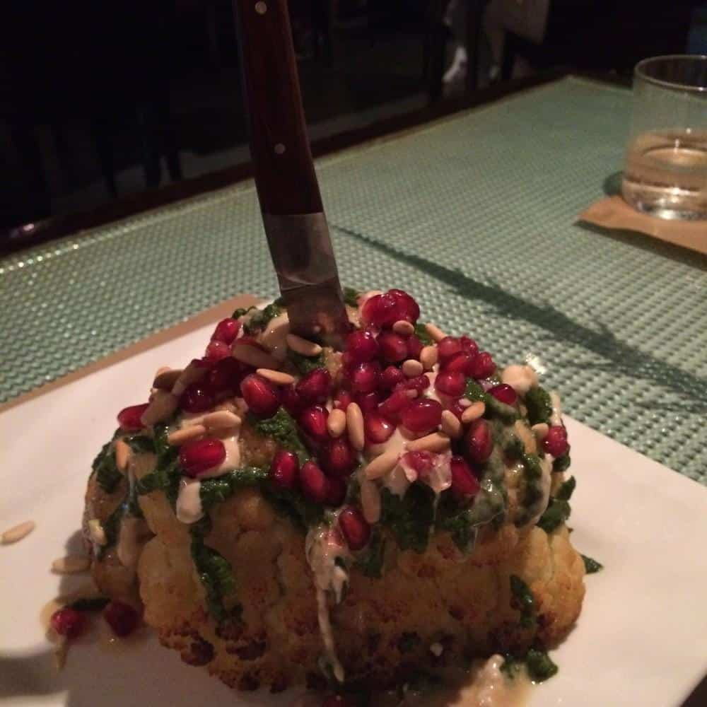 Cauliflower with tahini sauce, chilli and coriander salsa, pomegranate seeds and pine nuts