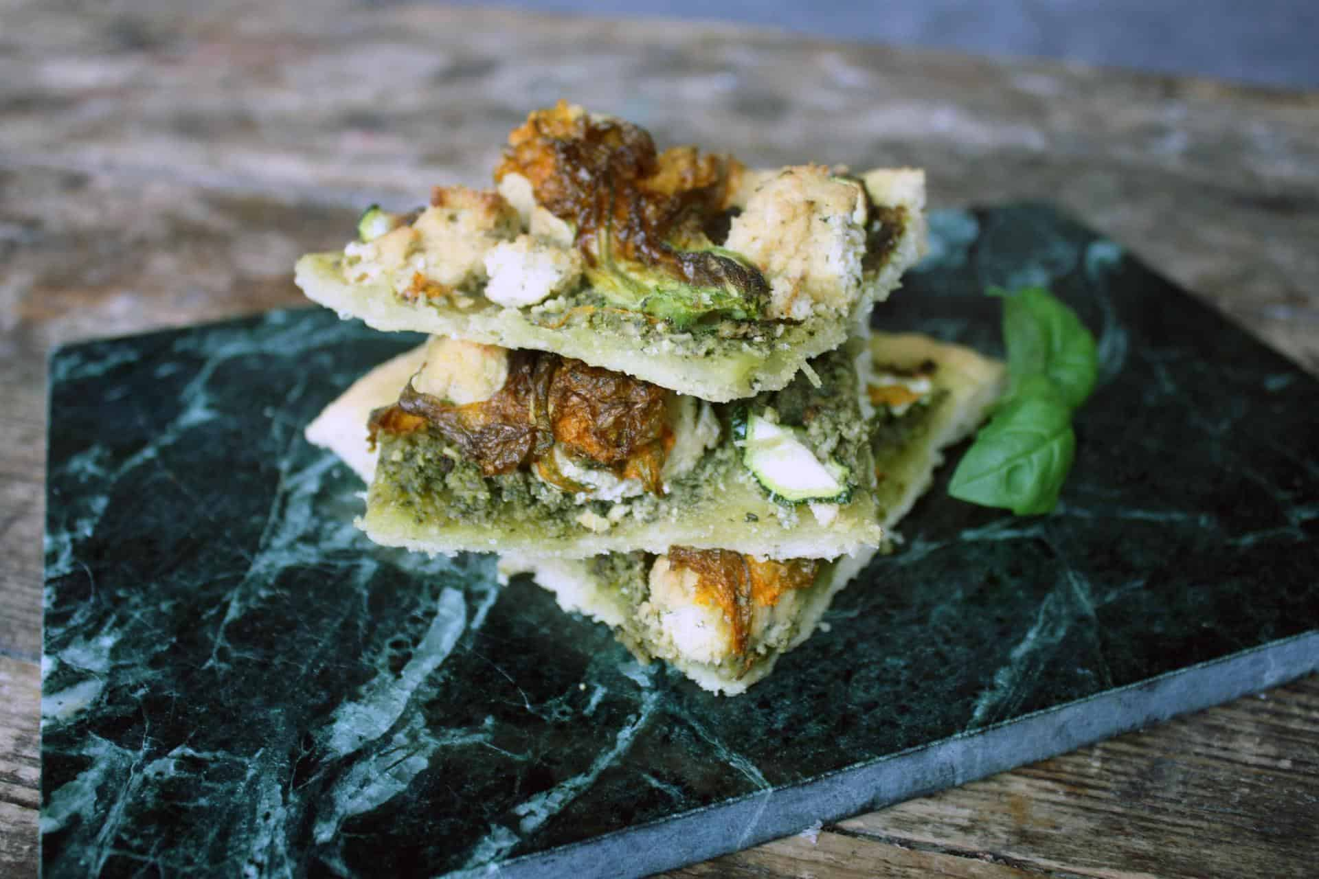 Pesto pizza with zucchini blossoms and cashew ricotta (vegan)