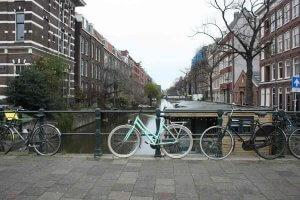 An Amsterdam canal with houseboats and bicycles