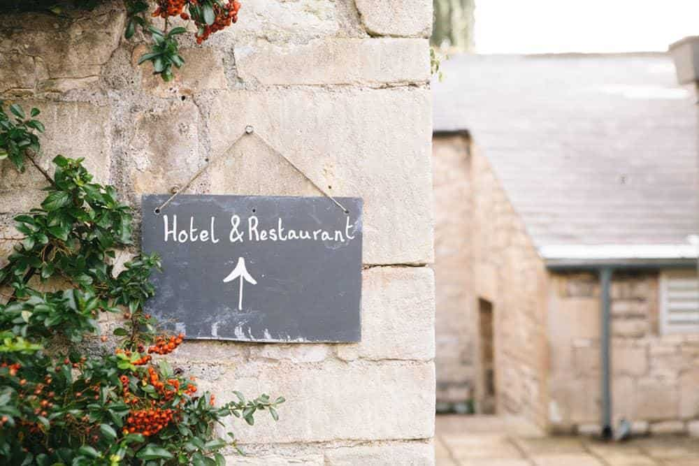 Chalkboard sign on stone wall that says 'hotel & restaurant'