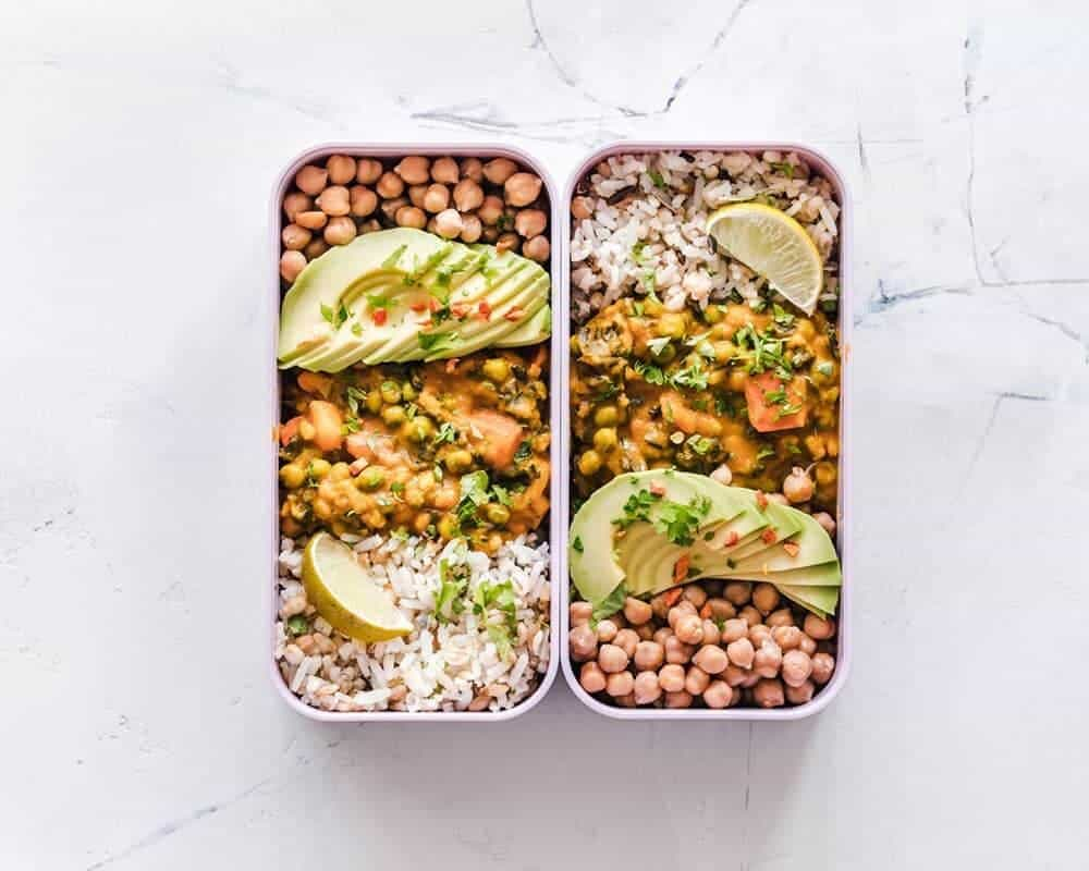 Two tupperware containing curry and rice. Vegan Food Delivery: the best vegan meal services available. Looking for vegan meal delivery near me? Here's where you find the best services to order vegan food delivered to your door.