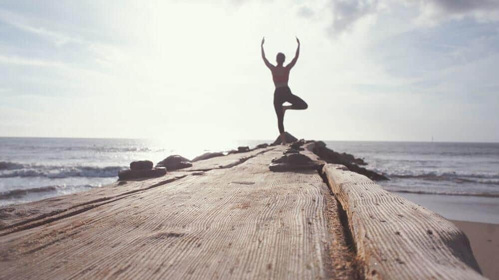 A person doing yoga on a pier with the sea in view