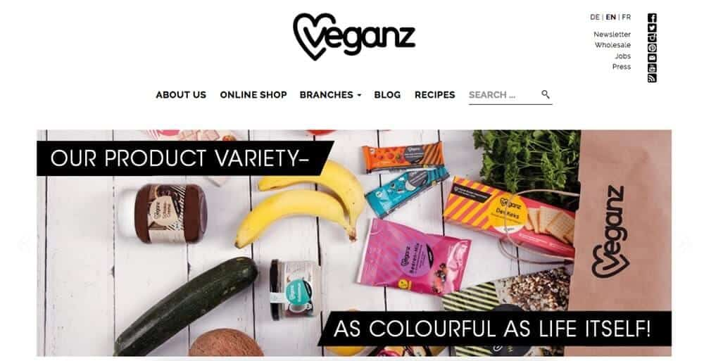 Screenshot of Veganz site showing a shopping bag with snacks, fruit and veg to one side