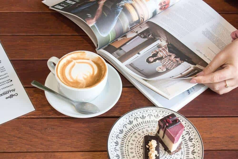 An open magazine, cup fo coffee and cake