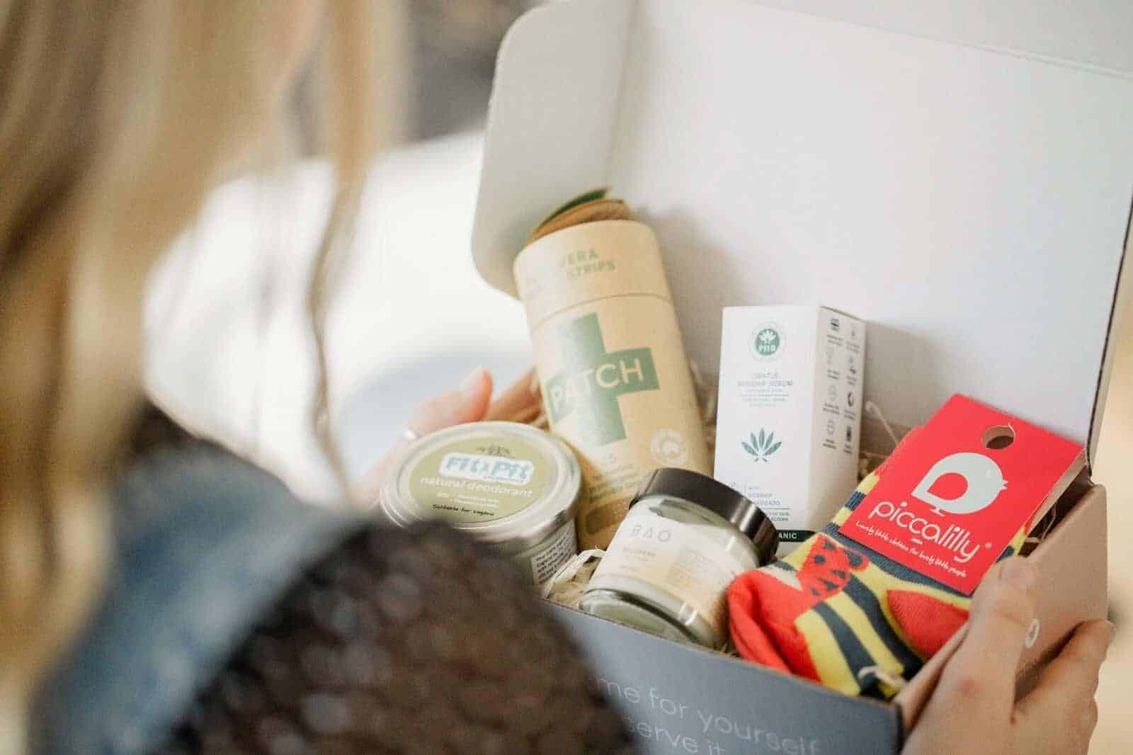 WOman holding a box containing socks, deodorant, plasters and more