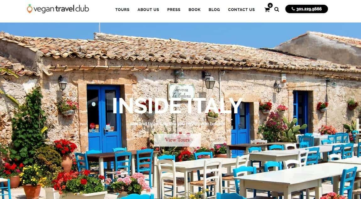 Screenshot of Vegan Travel Club page showing a stone cottage with colourful tables and chairs outside