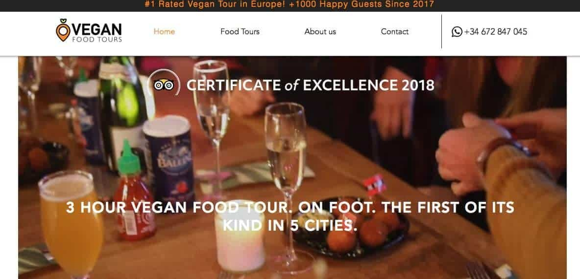 Screenshot of Vegan Food Tours showing glasses of champagne, glass of beer and food on a bar table