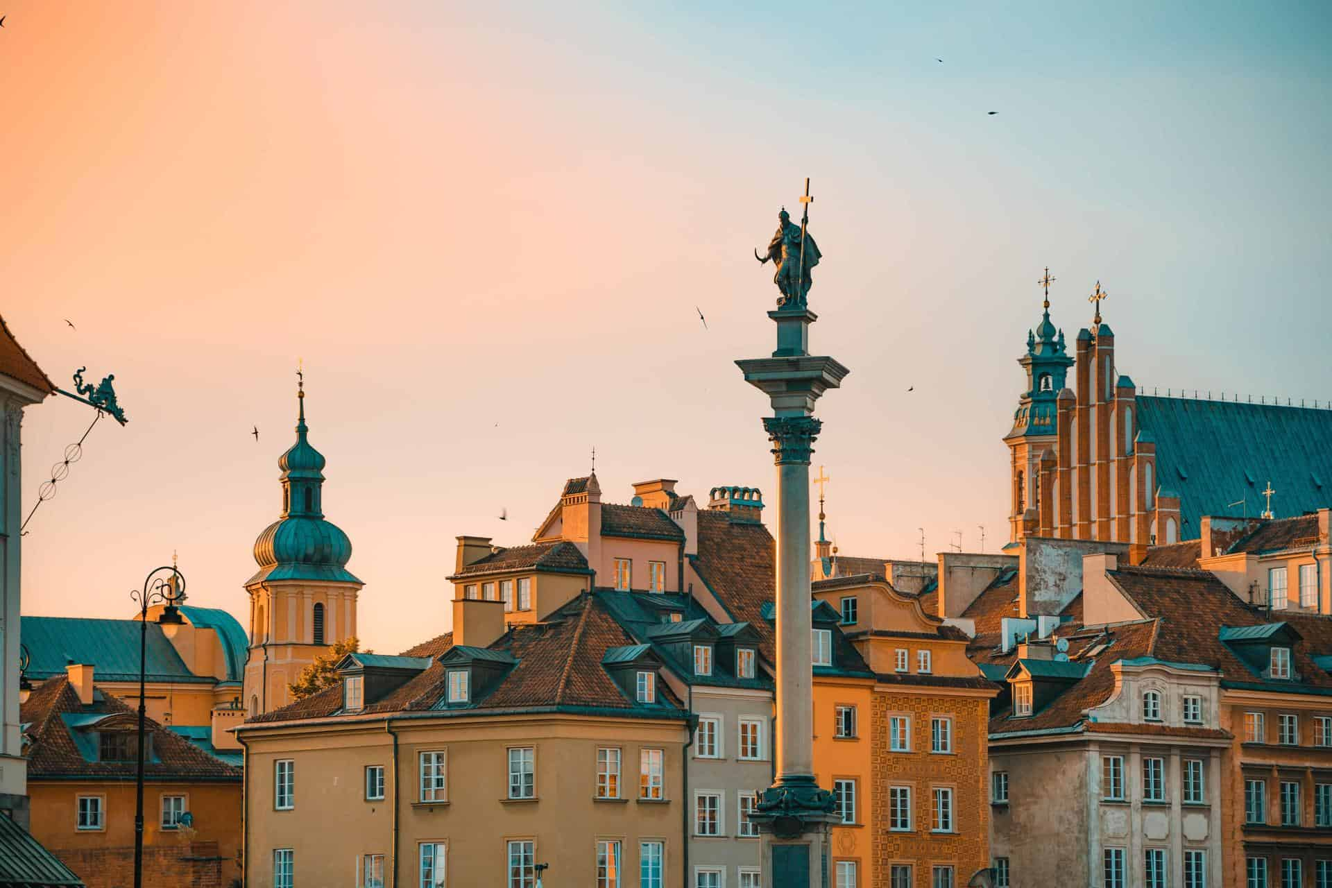 A statue on a column and tops of buildings