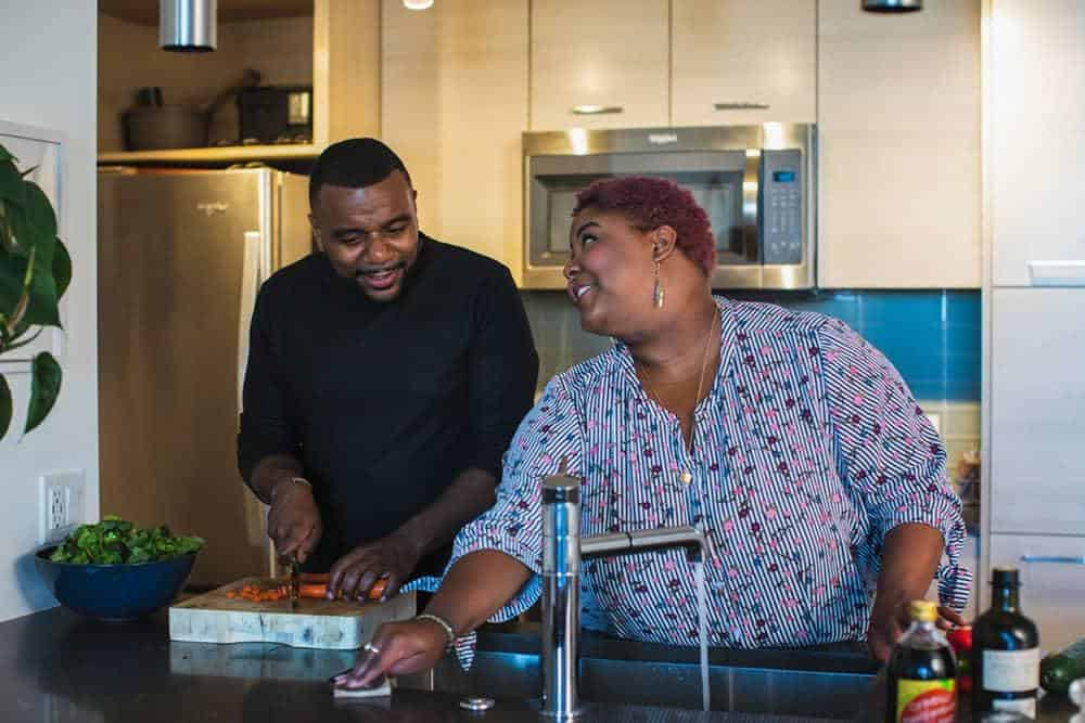 Couple cooking together: a man chops vegteables while the woman runs water in the sink. The best online vegan cooking classes reviewed.