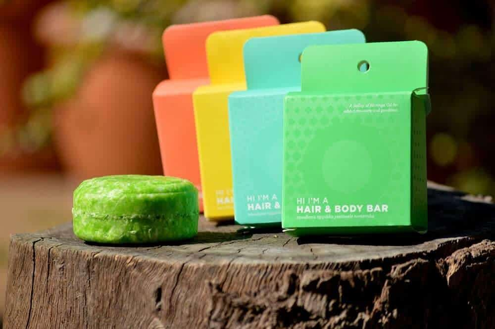 Row of colourful boxes with a solid shampoo bar next to them