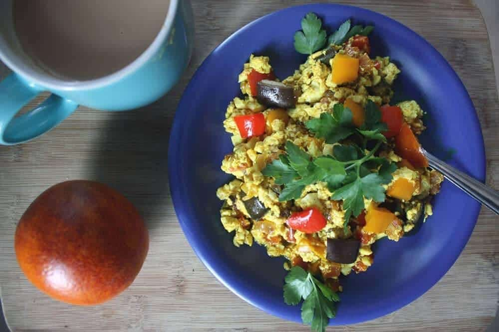 Colourful silken tofu scramble on a blue plate, with a mug of coffee and an orange.