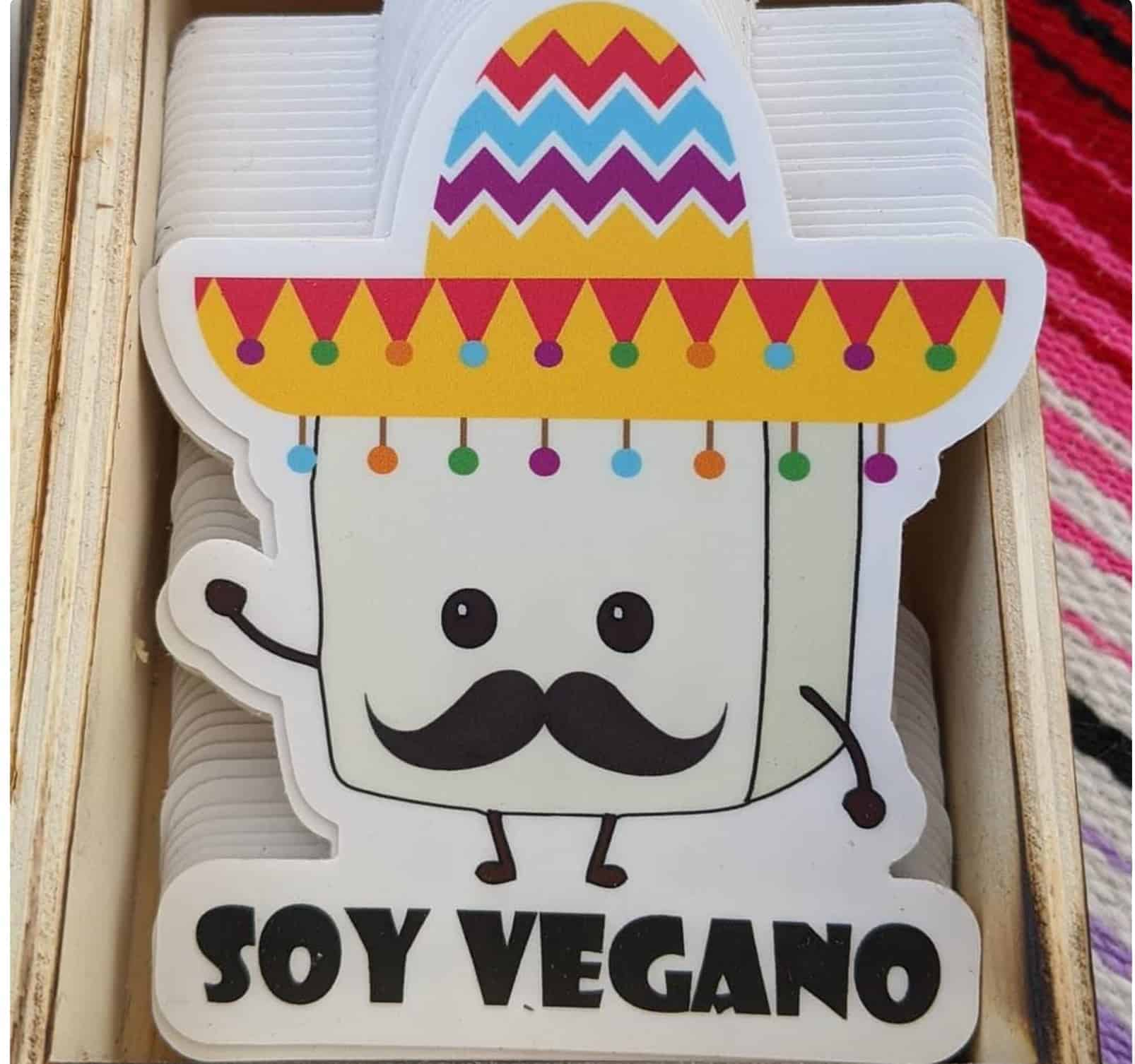 """Pin of a cartoon tofu with a moustache that says """"soy vegano"""""""